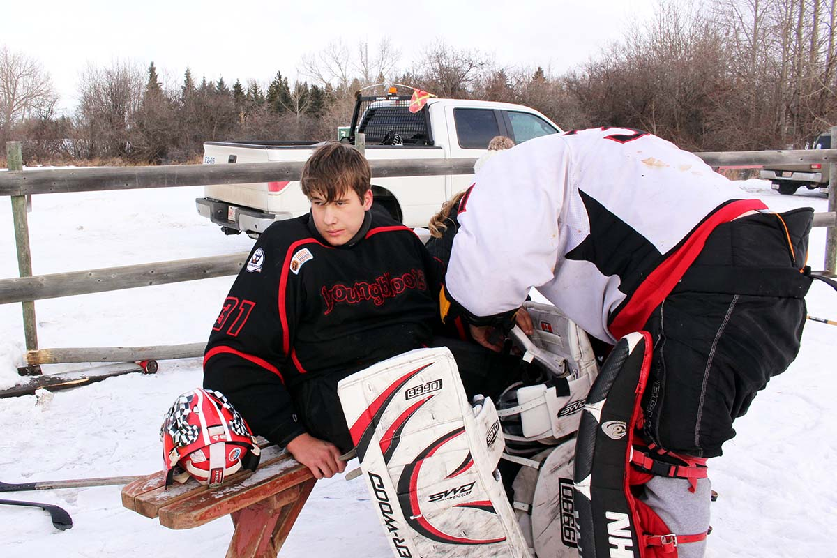 Chris, in all his goalie gear, tries to fix some loose straps on his son Peyton's goalie gear.